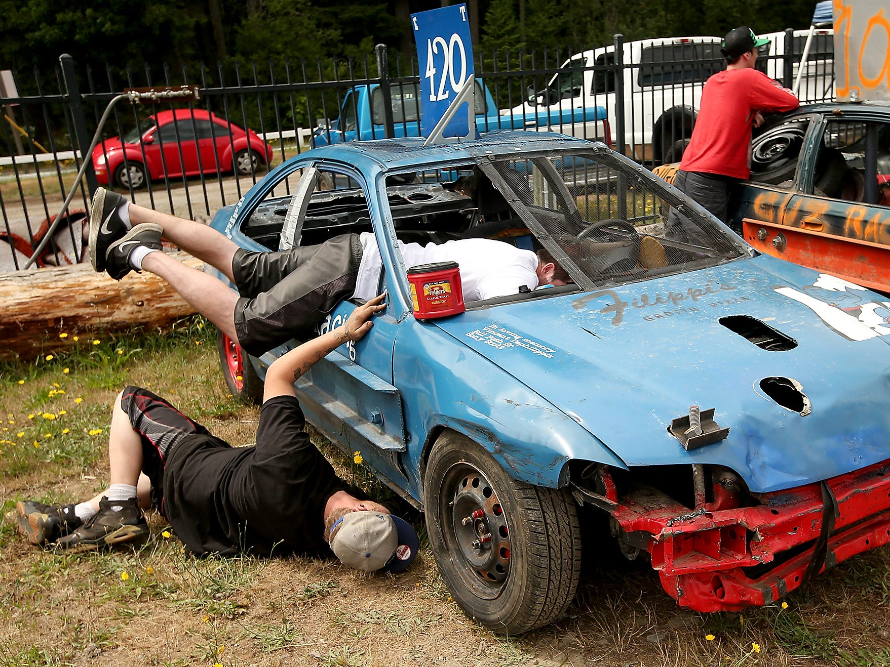 A car is worked on prior to the start of the Kitsap Destruction Derby on Saturday, June 23, 2018.