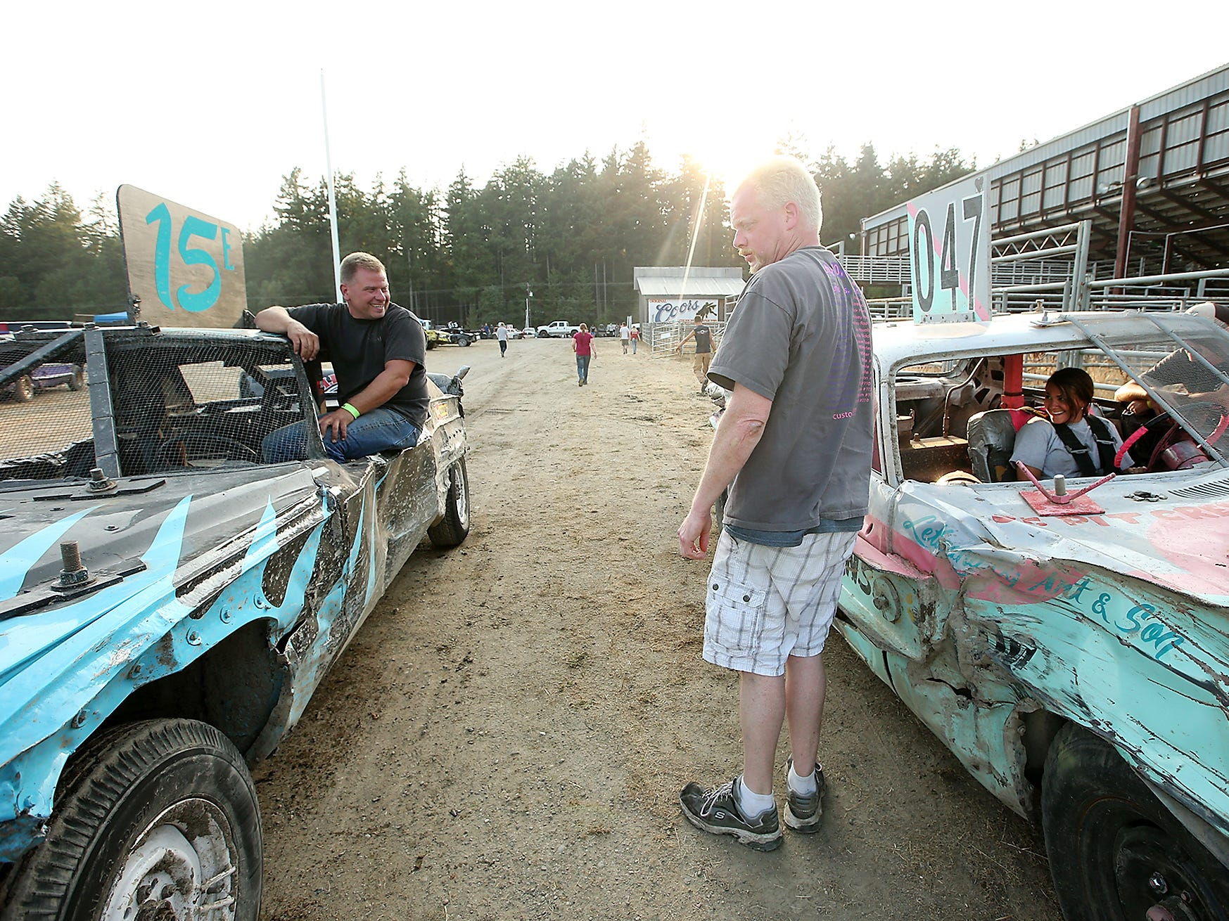 Drivers Dan Pieze (left) and Rachelle Ensor (right) talk between their cars as they line up and prepare for their next  race at the Kitsap County Fairgrounds on Saturday, July 28, 2018.