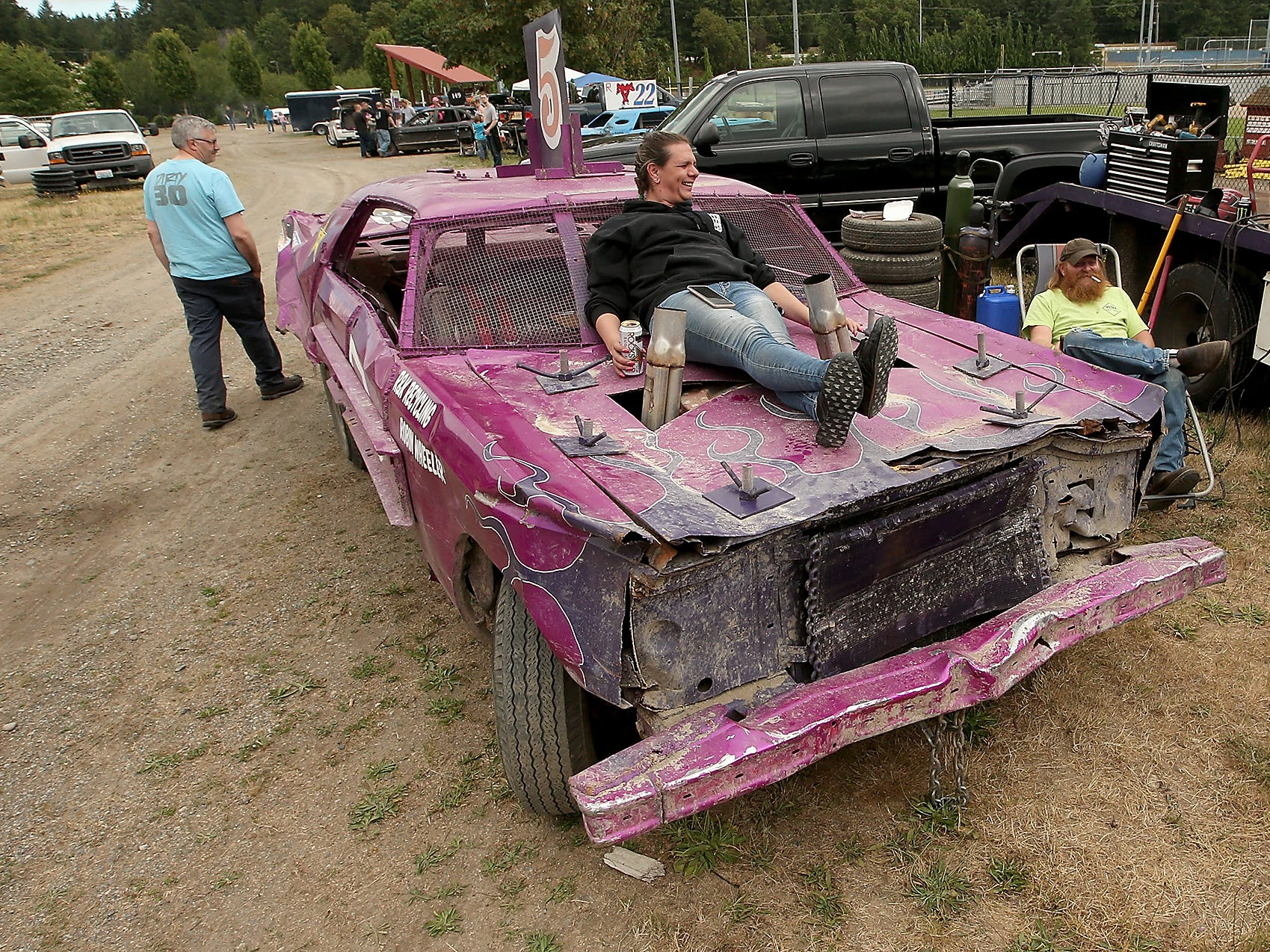 Driver Amber Aubele, of Bremerton, relaxes on the hood of her car with Pitman Ray Delander, of Shelton, (at right) as they await the start of the Kitsap Destruction Derby at Thunderbird Stadium on Saturday, June 23, 2018.