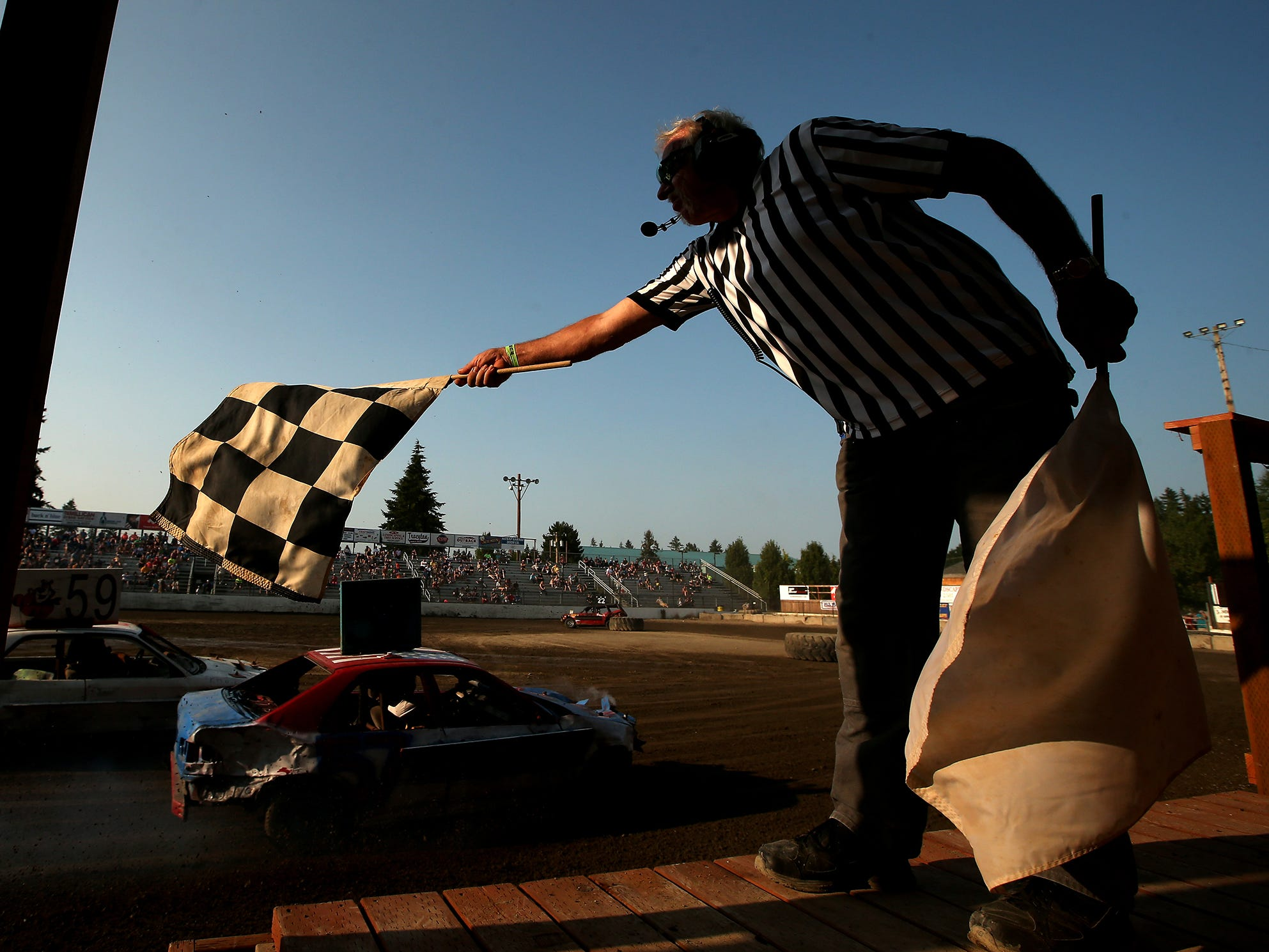 Official Flagger Mike Stevenson waves the checkered flag at the Kitsap Destruction Derby on Saturday, July 28, 2018.
