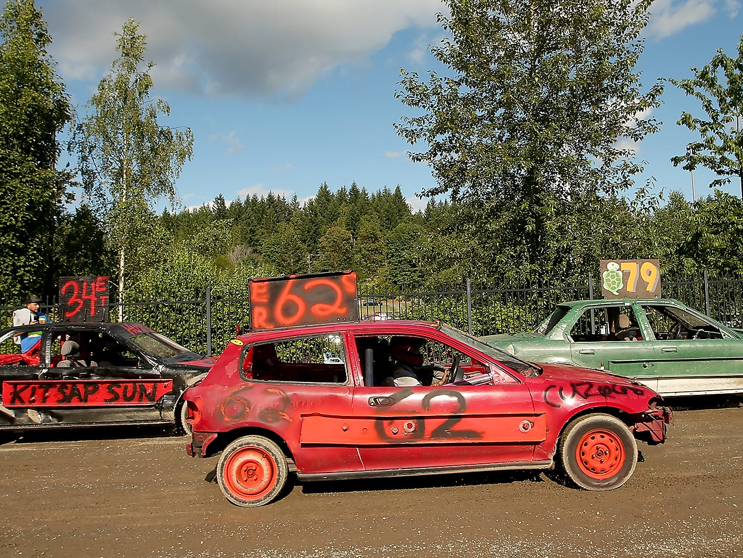 A trio of mini cars lines up prior to the start of their race for the Kitsap Destruction Derby on Saturday, June 23, 2018.