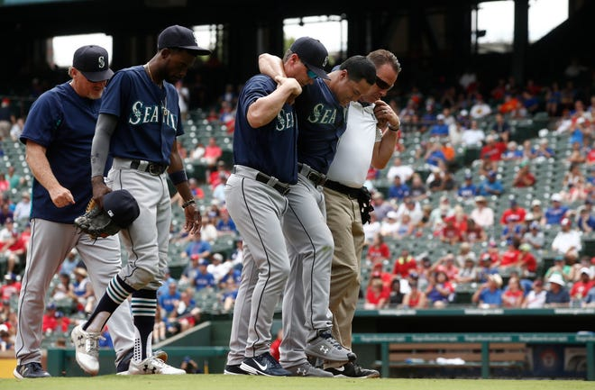 Mariners pitcher Sam Tuivailala is helped off the field after suffering an injury during the sixth inning.