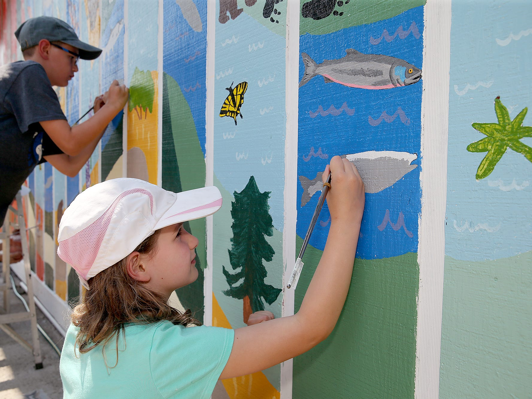 Lila O'Neil-Heine, 9, of Poulsbo volunteers to paint a salmon on the nature mural on Wednesday August 8, 2018.