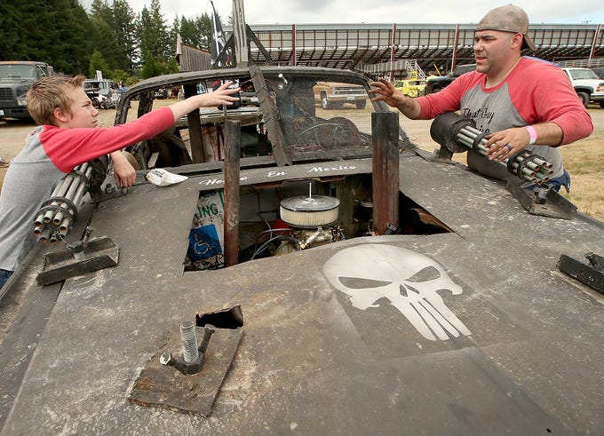 Pitman Zachary Lewis, 14, tosses a screw to his father Kevin as they attach the machine gun replicas to the hood of Kevin's car prior to the start of the Kitsap Destruction Derby at Thunderbird Stadium on Saturday, June 23, 2018.