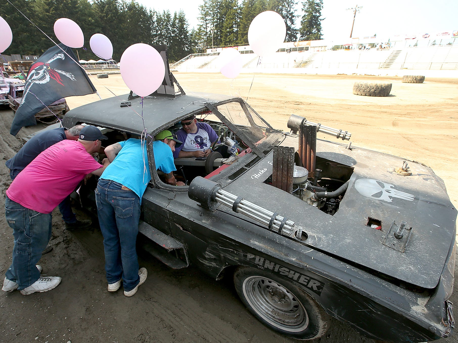 Kitsap Destruction Derby Association safety techs (left to right) KC Straight, Victor Trent and Dan Garrison peer into Kevin Lewis's car prior to the start of the Kitsap Destruction Derby at Thunderbird Arena at the Kitsap County Fairgrounds on Saturday, July 28, 2018.