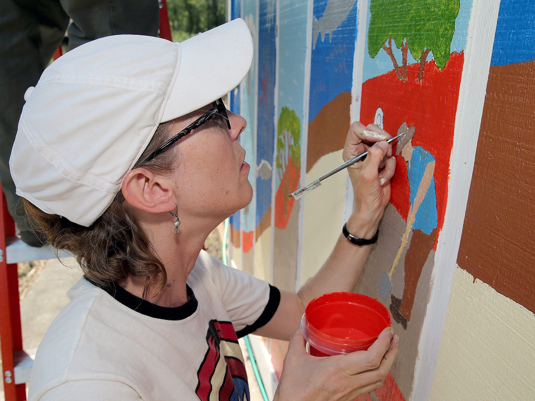 Mural artist Erica Applewhite of Poulsbo touches up the hat band colors to an image she designed of Clear Creek task Force legendary member Tex Lewis on the nature mural on Wednesday August 8, 2018.