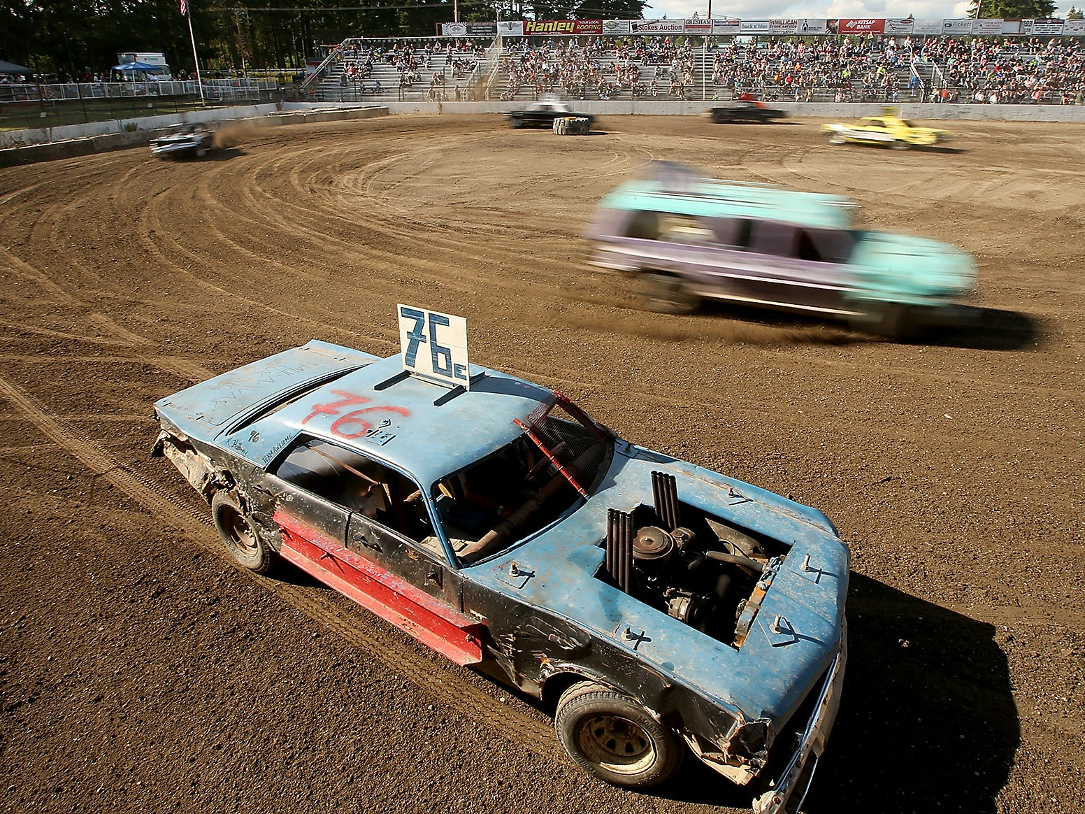 Cars continue to streak past as teh 76 car comes to a stop in the middle of the race during the Kitsap Destruction Derby Association derby at Thunderbird Stadium on Saturday, June 23, 2018.