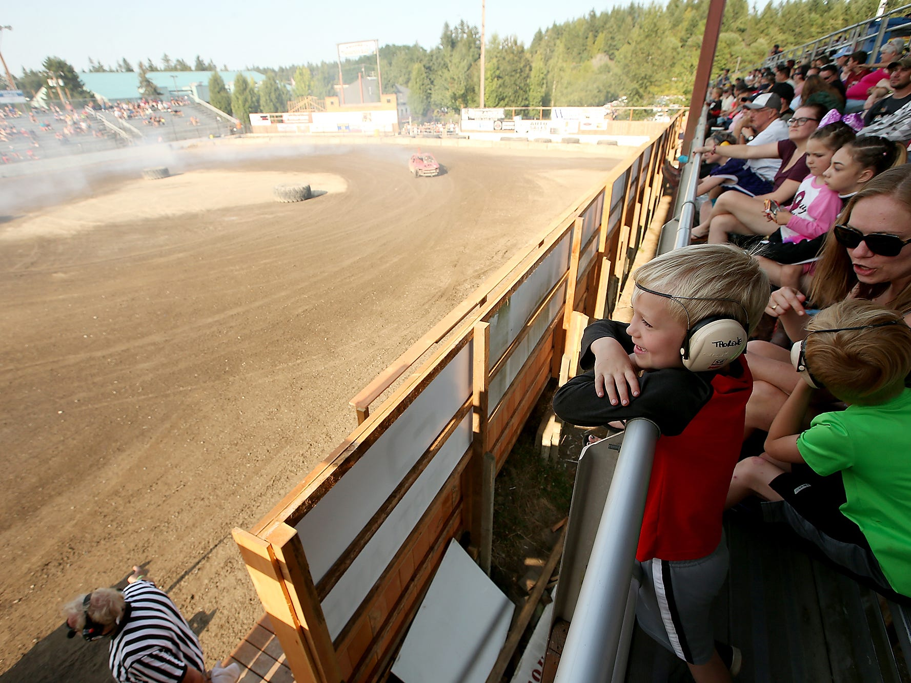 Alex Thorene, 6, of Seabeck, smiles as he watches the Kitsap Destruction Derby from the grandstands of Thunderbird Arena with his brother Connor, 7, and mother Heather on Saturday, July 28, 2018.