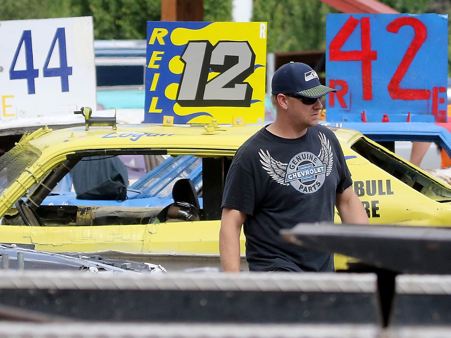 Driver Dan Garrison walks through the pit area prior to the start of the Kitsap Destruction Derby at Thunderbird Stadium on Saturday, June 23, 2018.