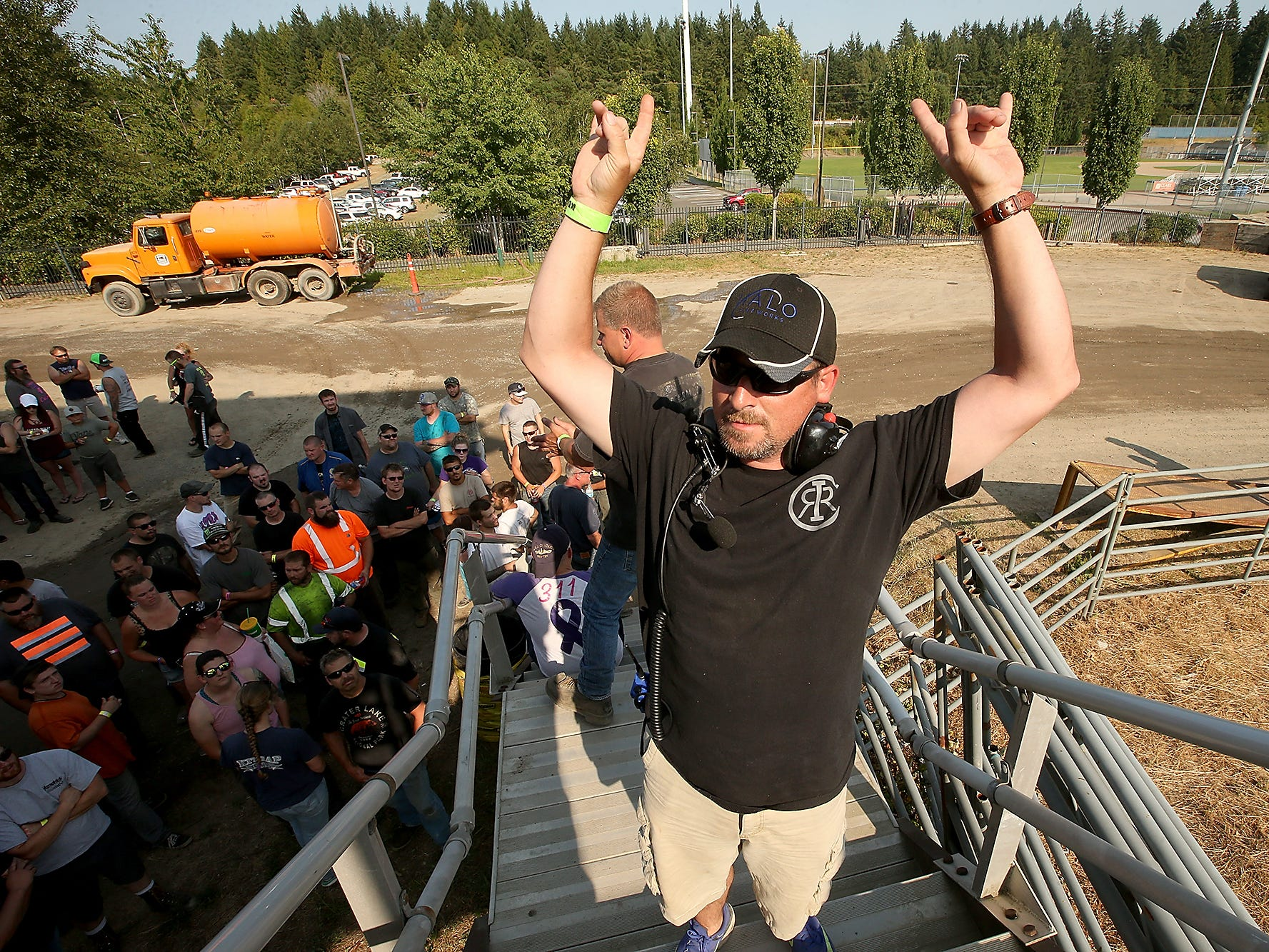 Head Judge Todd Williams throws his arms up in celebration after giving out the times from time trials at the driver's meeting prior to the start of the derby action on Saturday, July 28, 2018.