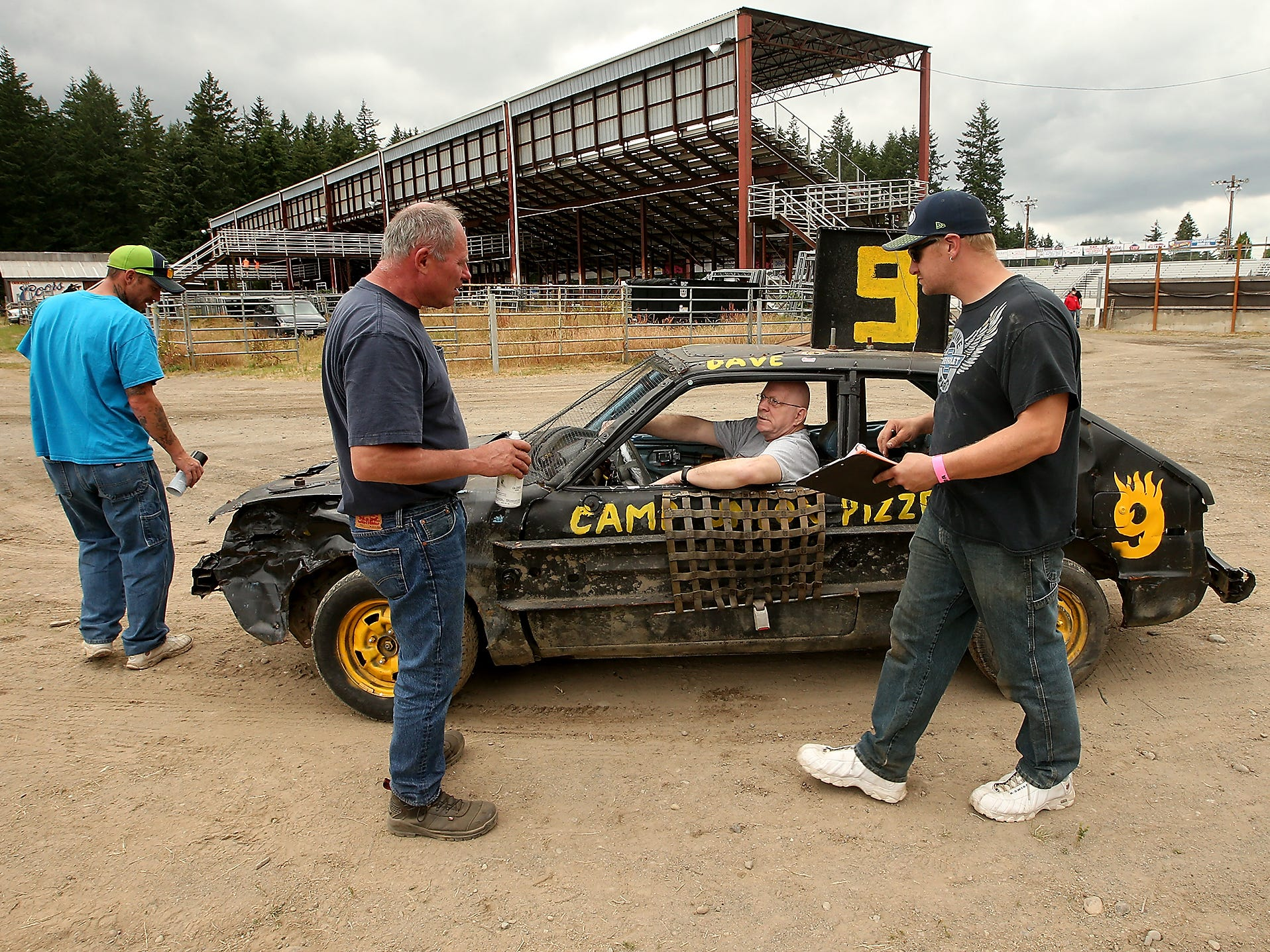 Kitsap Destruction Derby Association safety techs (left to right) Victor Trent, KC___ and Dan Garrison walk around driver David Lake's (center) car as they perform a safety check prior to the start of the Kitsap Destruction Derby at Thunderbird Stadium on Saturday, June 23, 2018.