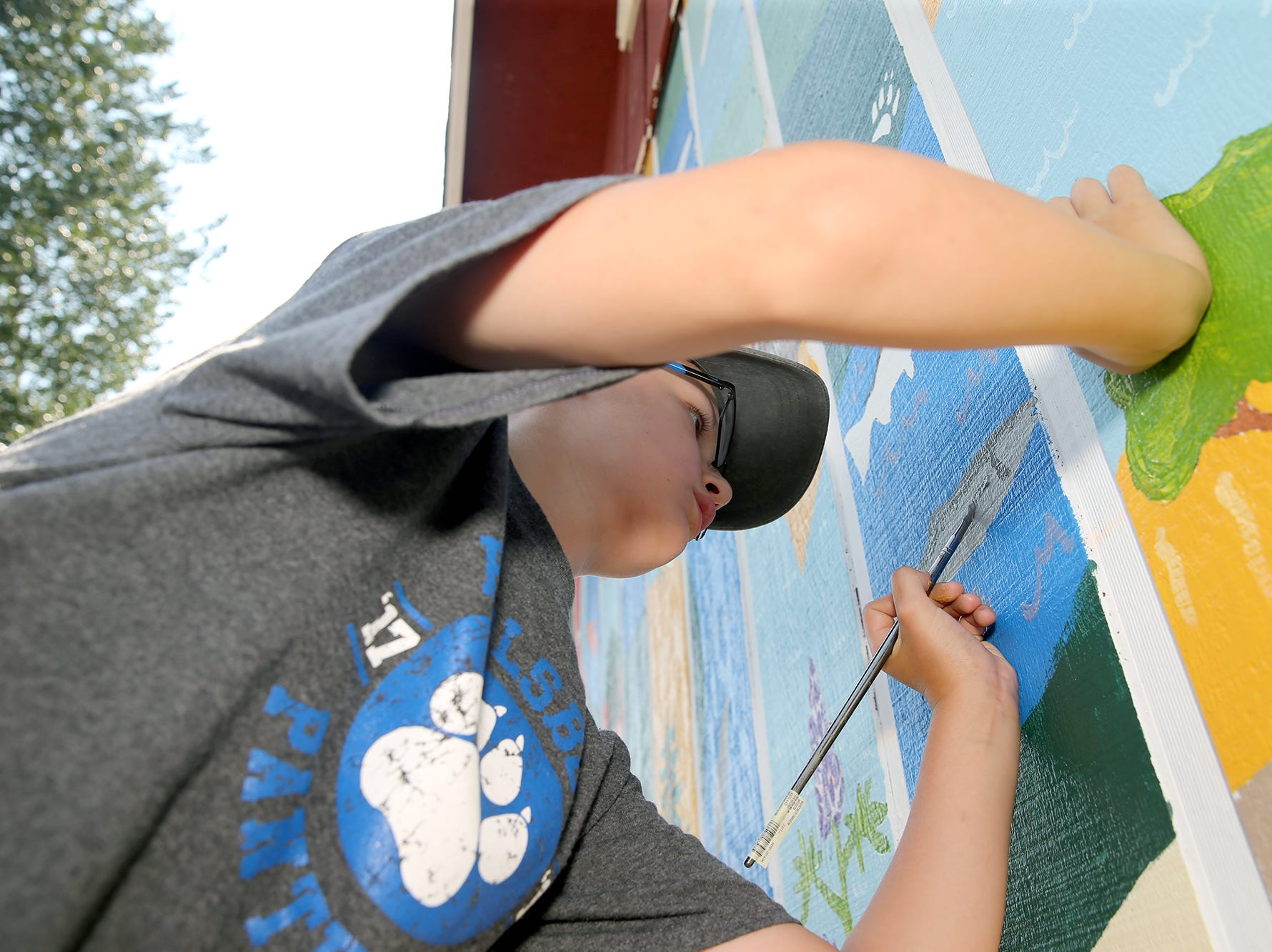 Soren O'Neil-Heine, 12, of Poulsbo volunteers to paint a salmon on the nature mural on Wednesday August 8, 2018.