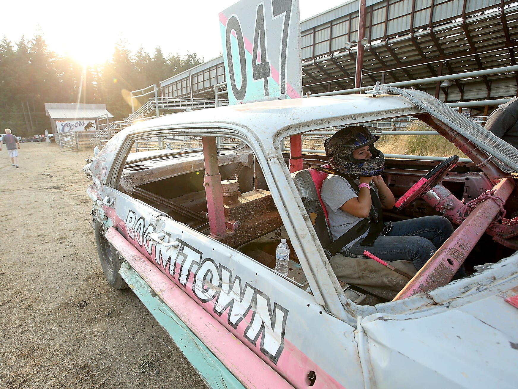 Driver Rachelle Ensor secures her helmet as she preapres to enter the track for the Kitsap Destruction Derby at Thunderbird Arena at the Kitsap County Fairgrounds on Saturday, July 28, 2018.