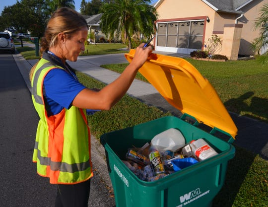 Michelle Smith, Melbourne environmental programs coordinator, checks a recycling cart Wednesday morning in the Feather Lakes neighborhood.