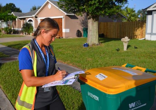Michelle Smith, Melbourne environmental programs coordinator, checks a recycling cart in the Feather Lakes neighborhood.