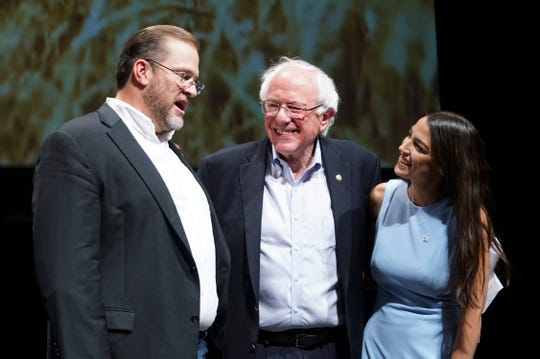 Kansas congressional candidate James Thompson, left, U.S Sen. Bernie Sanders, I-Vt.,  and Alexandria Ocasio-Cortez, a Democratic congressional candidate from New York, stand together on stage after a rally, Friday, July 20, 2018, in Wichita, Kan.