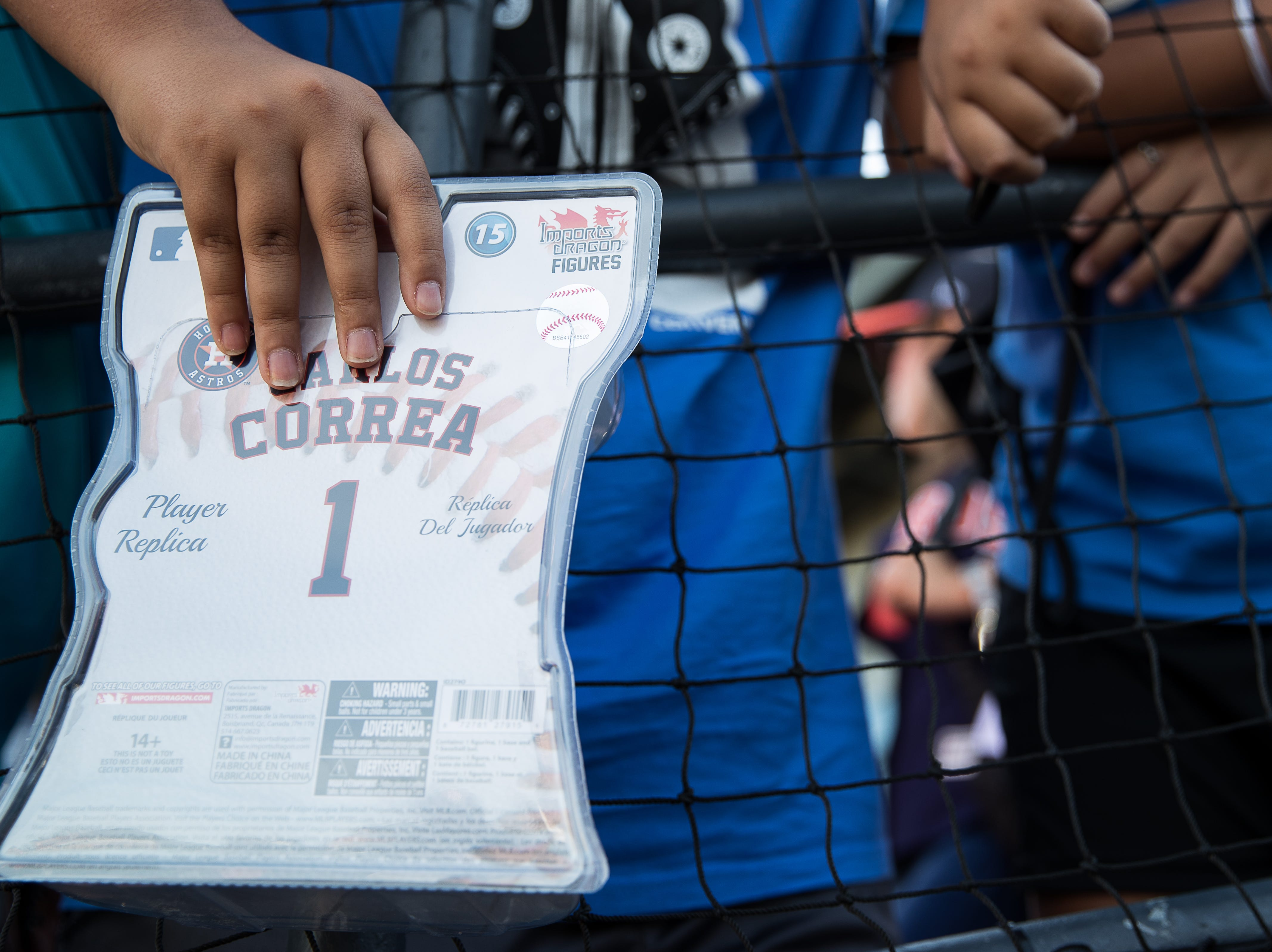 A young fan holds a Carlos Correa toy as he stands outside the home team tunnel at Whataburger Field before a Hooks game where Correa is playing on a rehab assignment Tuesday, Aug. 7, 2018.