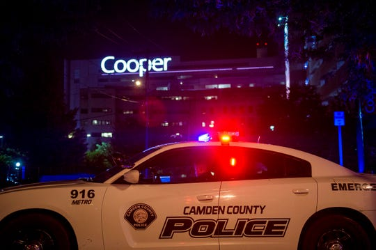 An officer is posted by Copper hospital following a shooting that left two detectives wounded Tuesday evening, Aug. 7, 2018 in Camden, N.J.