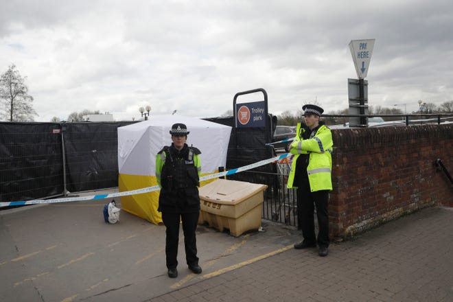 In this March 13, 2018, file photo, police officers guard a cordon around a police tent covering a supermarket car park pay machine near the spot where former Russian spy Sergei Skripal and his daughter were found critically ill following exposure to the Russian-developed nerve agent Novichok in Salisbury, England. The United States will impose sanctions on Russia for the country's use of a nerve agent in an assassination attempt on a former Russian spy and his daughter. The State Department says Aug. 8, sanctions will be imposed on Russia as the country used chemical or biological weapons in violation of international law.