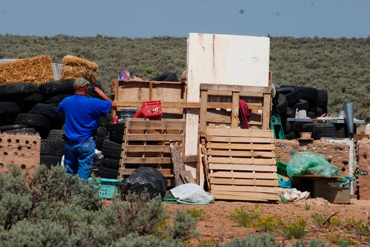 Taos County Solid Waste Department Director Edward Martinez surveys property conditions at a disheveled living compound at Amalia, N.M., Tuesday, Aug. 7, 2018. The investigation into a group of starving children found in the desert compound in New Mexico took another dark turn Tuesday, when authorities said they found the remains of a young boy at the squalid property.