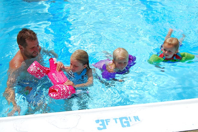 Several years ago from left, Alex Workman, of Burlington, swims with his children Brooke, Alyssa, and Colin, at the Union Pool.