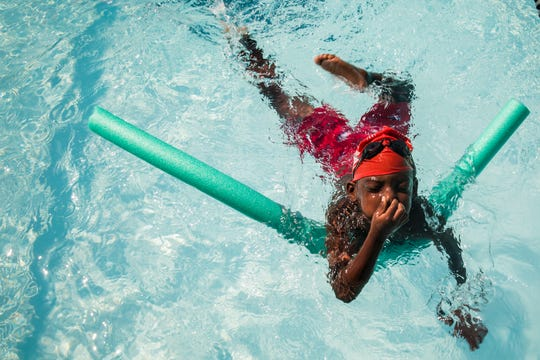 """Mosaiah Epps swims with the help of a noodle during a July practice. """"I love their love for learning and swimming and how much they've grown,"""" Coach Emma Vansteenkiste said."""