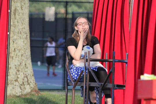"""Juliet (Petrea Whittier) ponders her new-found love, Romeo, while a basketball game continues uninterrupted in the background. This scene unfolded during a 2015 Shakespeare in the Park production of """"Romeo and Juliet"""" in Deerfield Township."""