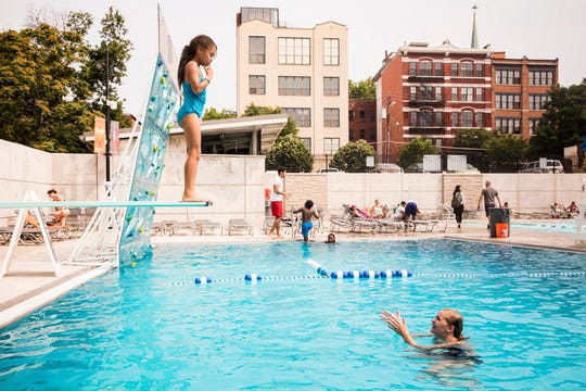 Aria Groomes hesitates before jumping off the diving board at Ziegler Park. Coach Emma Vansteenkiste waits below. The swim team organizers aimed for the program to help the children feel safe, strong and confident in the water.