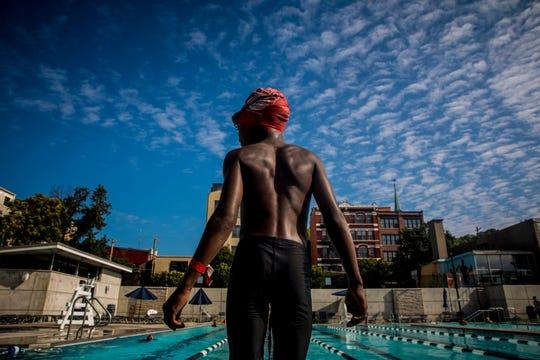 Jayden Davis stands on the edge of the pool.