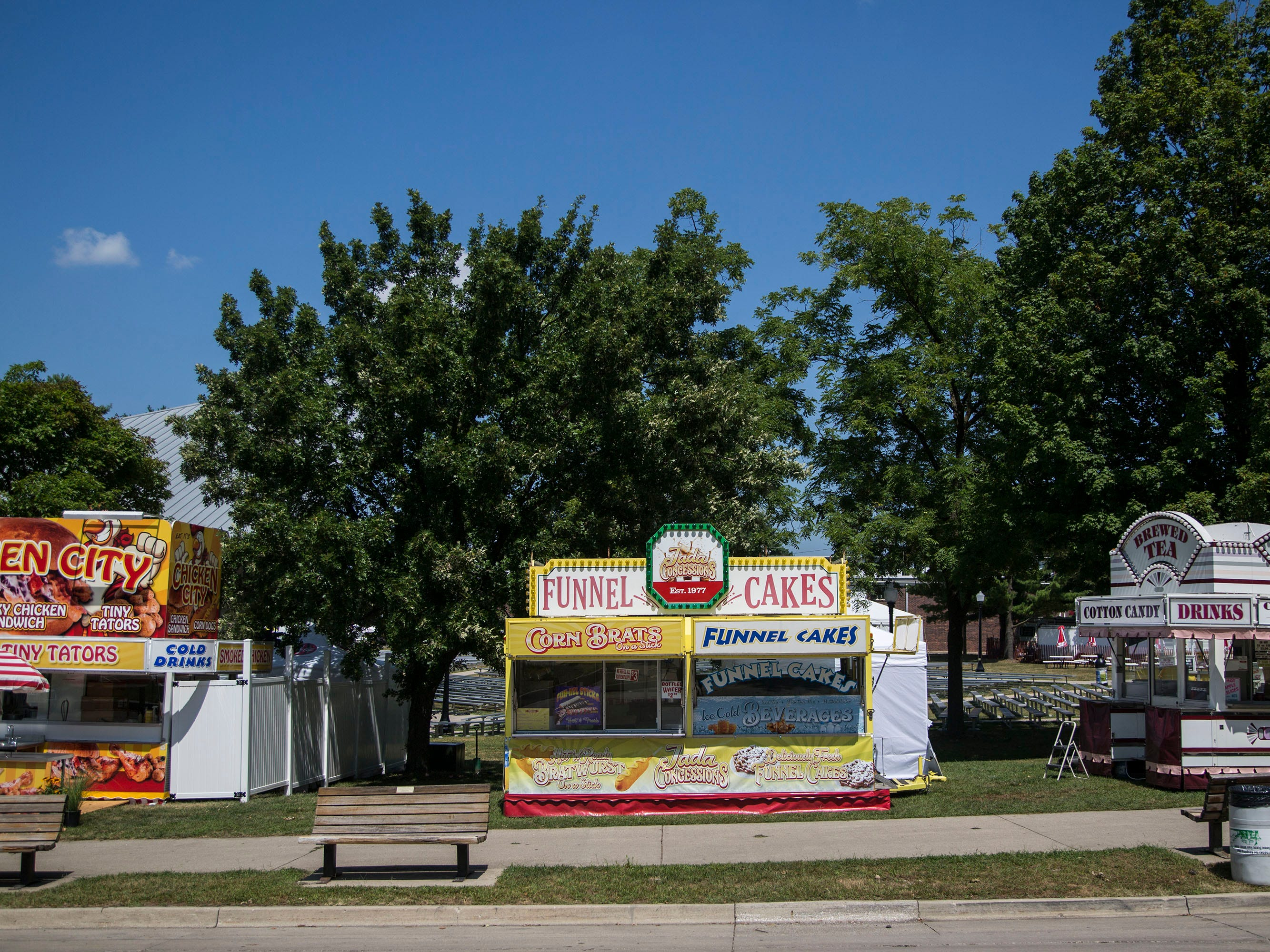 Jada Smith's funnel cake stand sits in a sunny spot at the base of a hill on Grand Avenue at Iowa State Fair on Wednesday, Aug. 8, 2018, the day before the fair begins.
