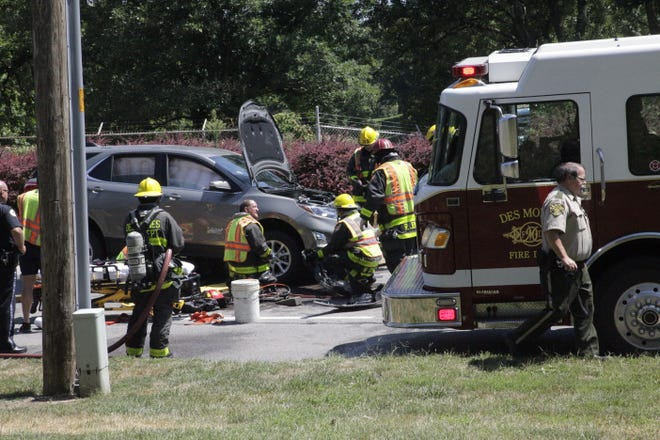 Des Moines Fire Department crews prepare to extract a motorcyclist from under an SUV after the two vehicles crashed, dragging the man for about 300 feet on Fleur Drive on Wednesday, Aug. 8, 2018.