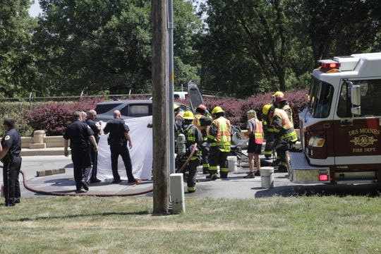 Des Moines fire and police crews prepare to extract a motorcyclist from under an SUV after the two vehicles crashed, dragging the man for about 300 feet on Fleur Drive on Wednesday, Aug. 8, 2018.