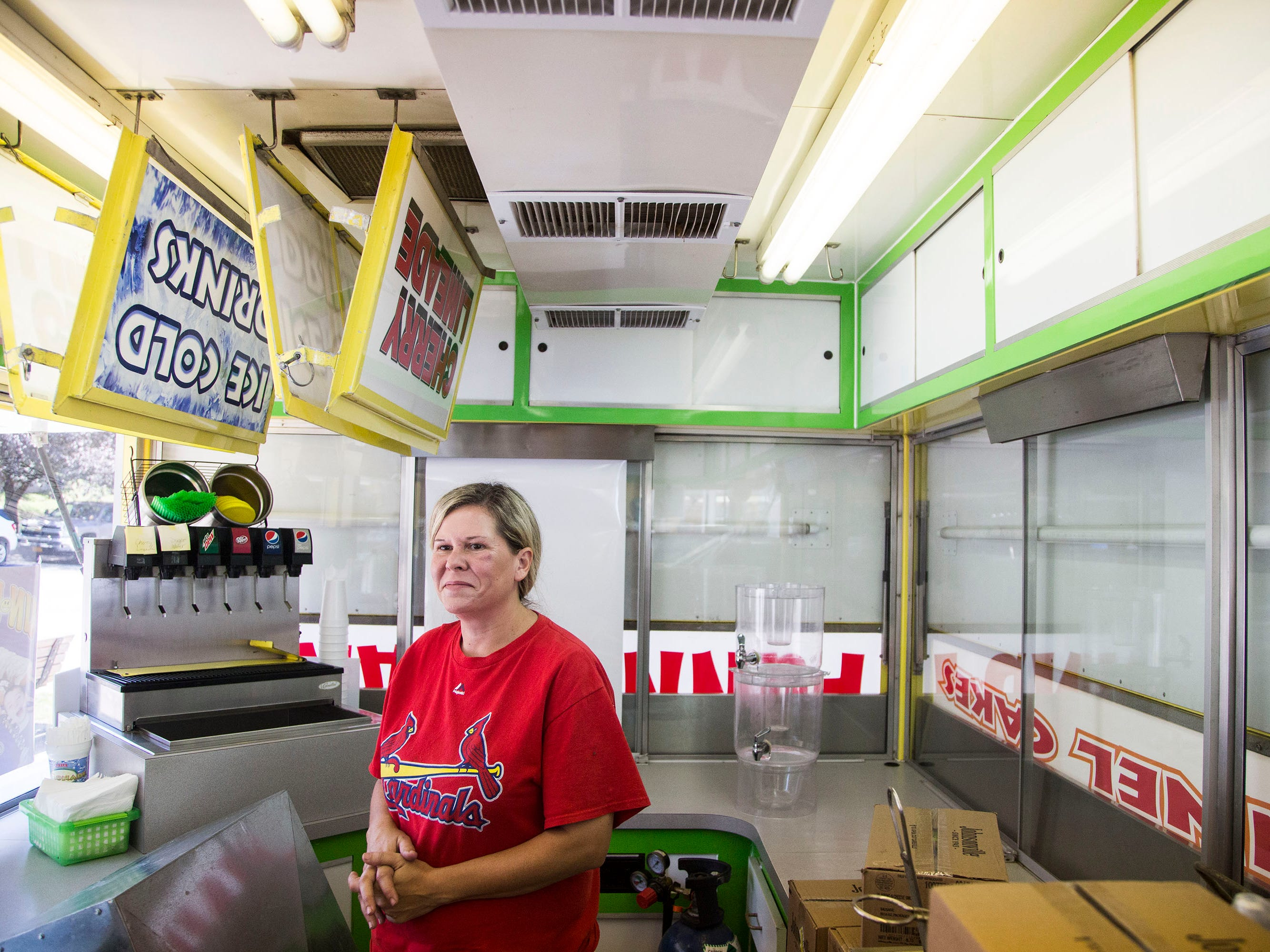 Jada Smith, owner of Jada Concessions, stands inside her funnel cake trailer on the Iowa State Fairgrounds on Wednesday, Aug. 8, 2018, the day before the fair begins. This is Smith's first time back at the fair selling her family's funnel cakes since 1997, the year after her parents were murdered at the fair.