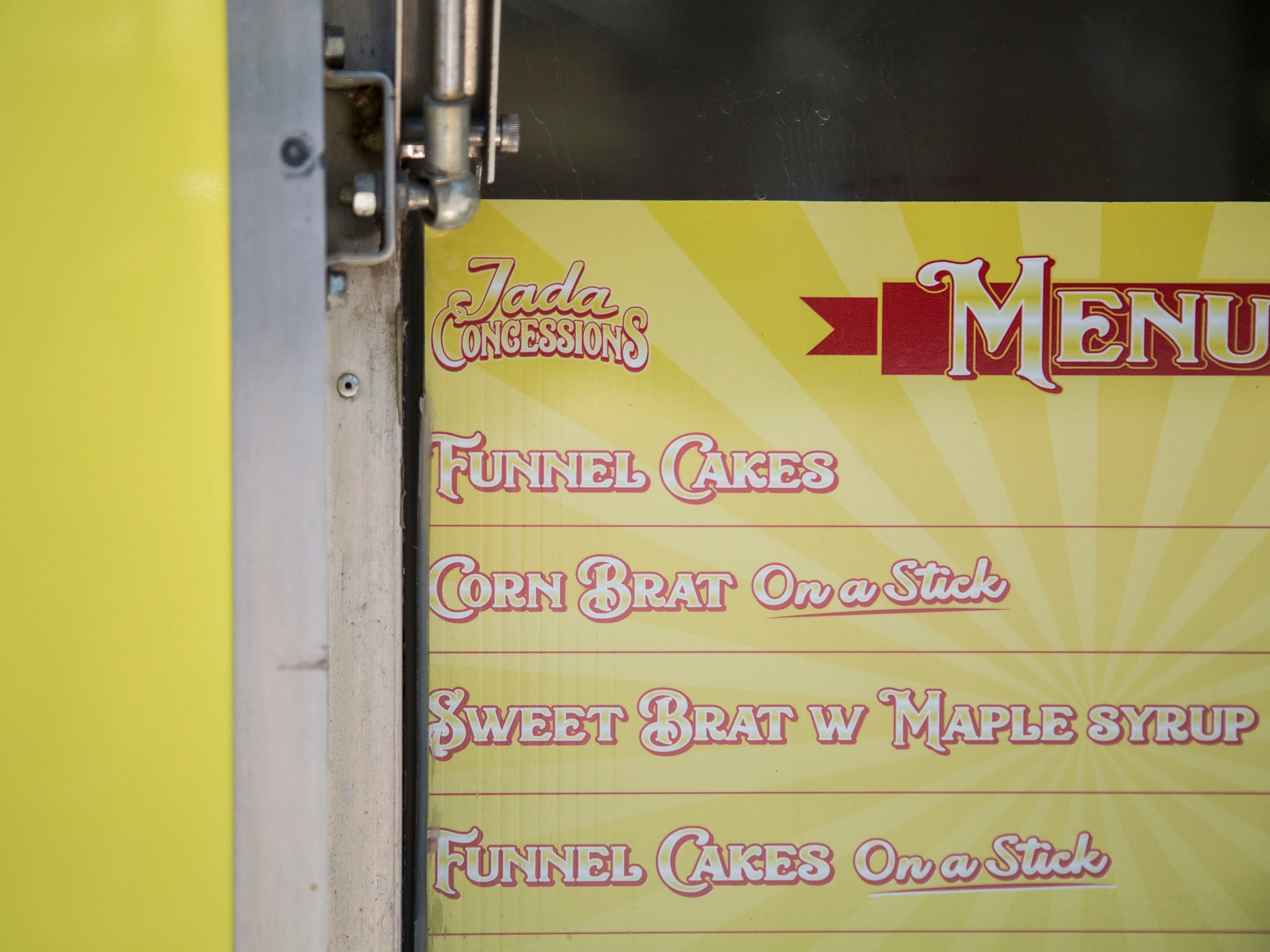 The posted menu at Jada Smith's funnel cake stand includes funnel cakes, funnel cake on a stick and a version of corndogs made with brats on Wednesday, Aug. 8, 2018, at the Iowa State Fair.
