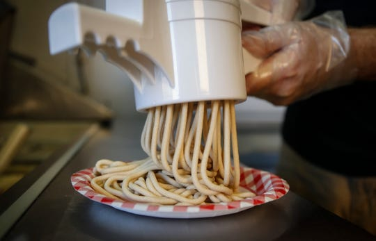 Dennis Mitchell of Coralville makes a plate of Cookie Dough Spaghetti at the Dipped In Chocolate stand at the Pavilion on the Iowa State Fair grounds.