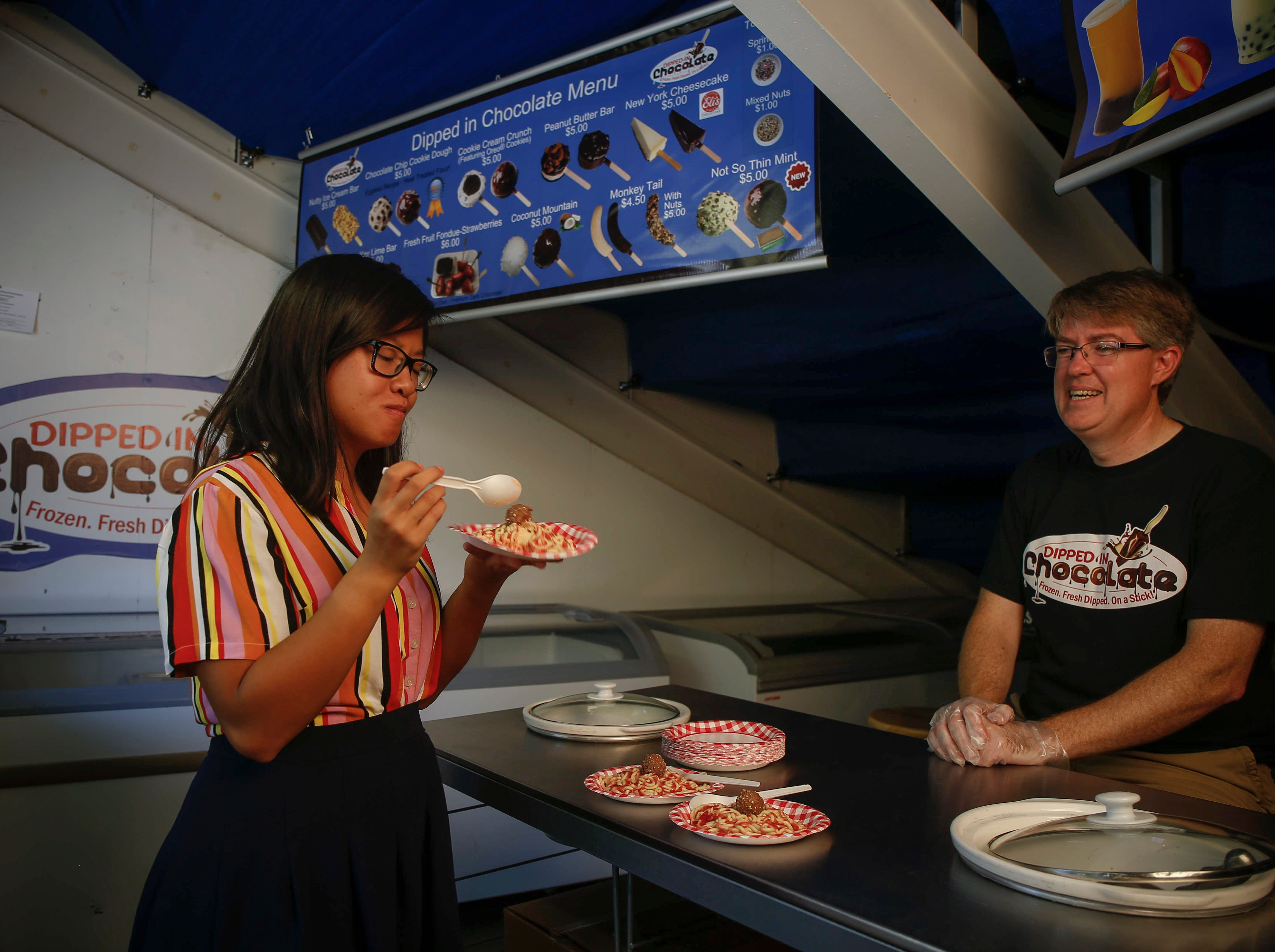 Des Moines Register reporter Linh Ta tries a bite of Cookie Dough Spaghetti which was co-created by Dennis Mitchell, right, at the Dipped In Chocolate stand at the Pavilion on the Iowa State Fair grounds.