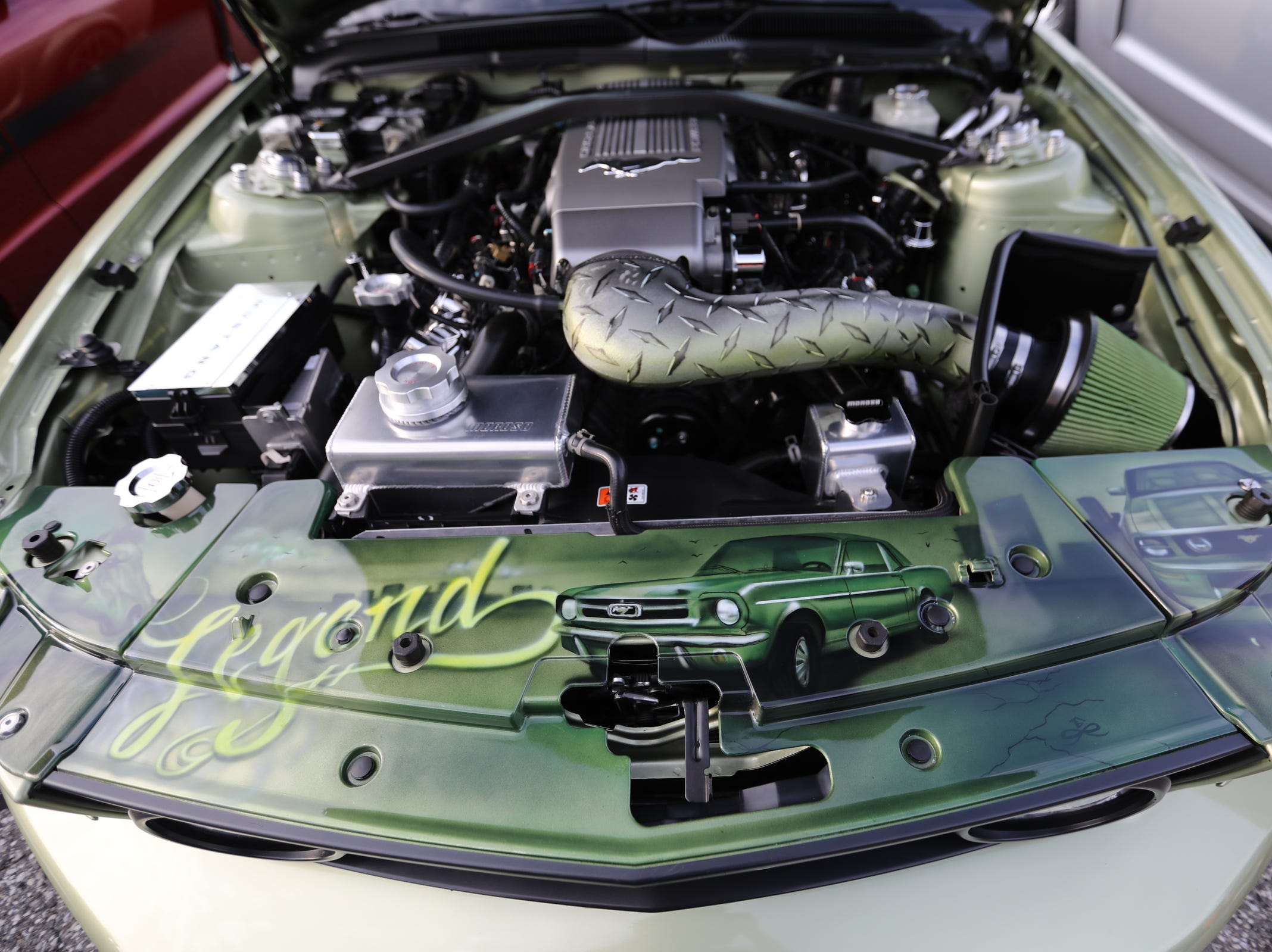The engine of a 2006 Ford Mustang GT convertible owned by Peter Dunbar, 63, of Detroit has a custom paint job seen during a Ford event celebrating the 10,000,000 Mustang built at the Ford Motor Company World Headquarters in Dearborn on Wed., Aug 8, 2018.