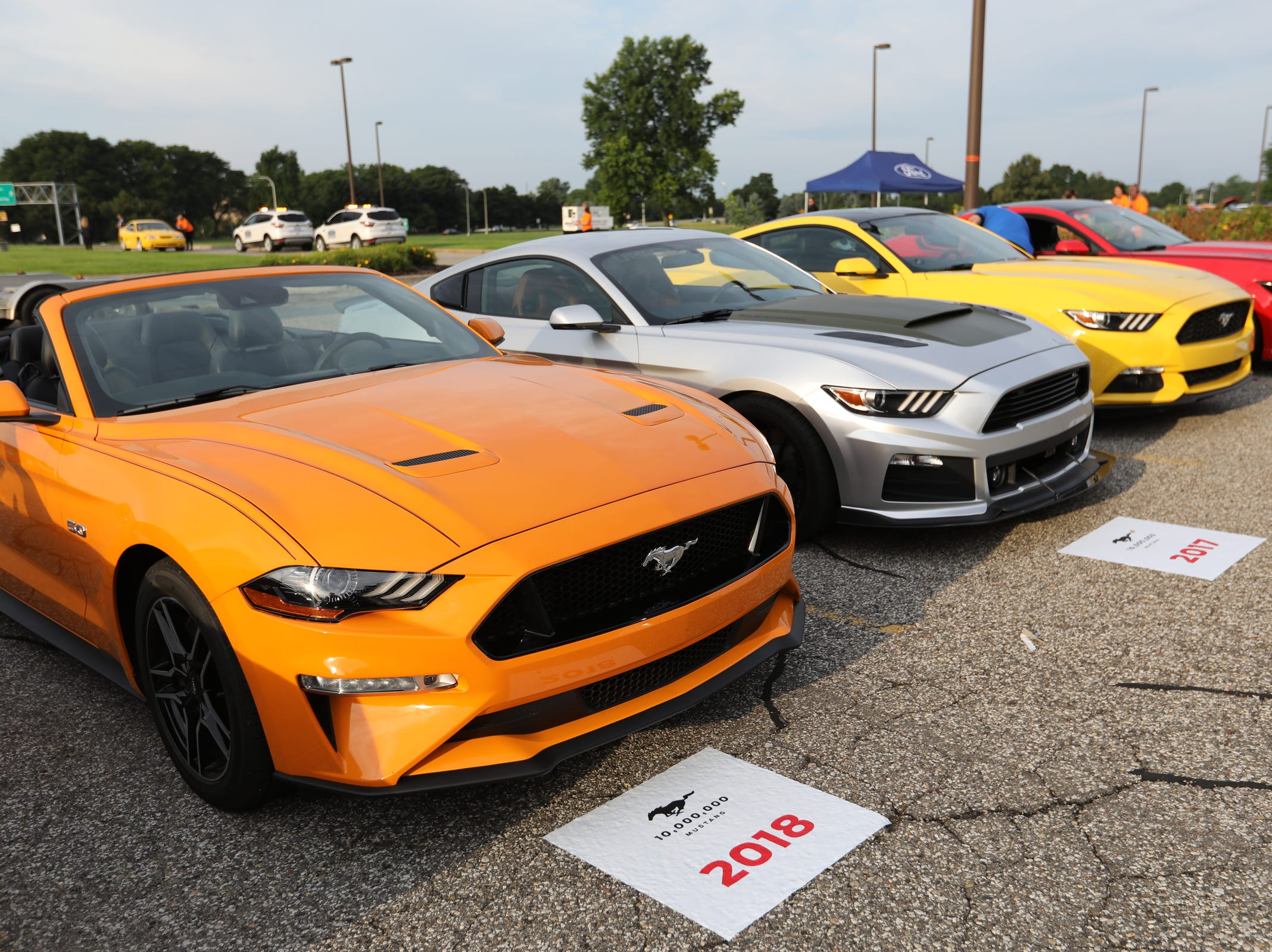 New Ford Mustangs from 2018 to 2015 are lined up in the parking lot during a Ford event celebrating the 10,000,000 Mustang built at the Ford Motor Company World Headquarters in Dearborn on Wed., Aug 8, 2018.