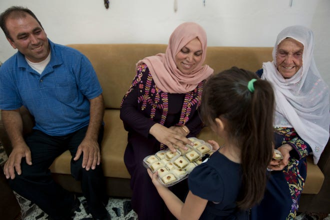 In this Wednesday, Aug. 8, 2018, photo, a Palestinian girl offers sweets to family members of Rashida Tlaib — aunt Fadwa, center, grandmother Muftiyeh, right and uncle Bassam — as they celebrate Rashida's U.S. election victory, at the family house, in the West Bank village of Beit Ur al-Foqa. The Michigan primary victory of Tlaib, who is expected to become the first Muslim woman and Palestinian-American to serve in the U.S. Congress, is rippling across the Middle East.