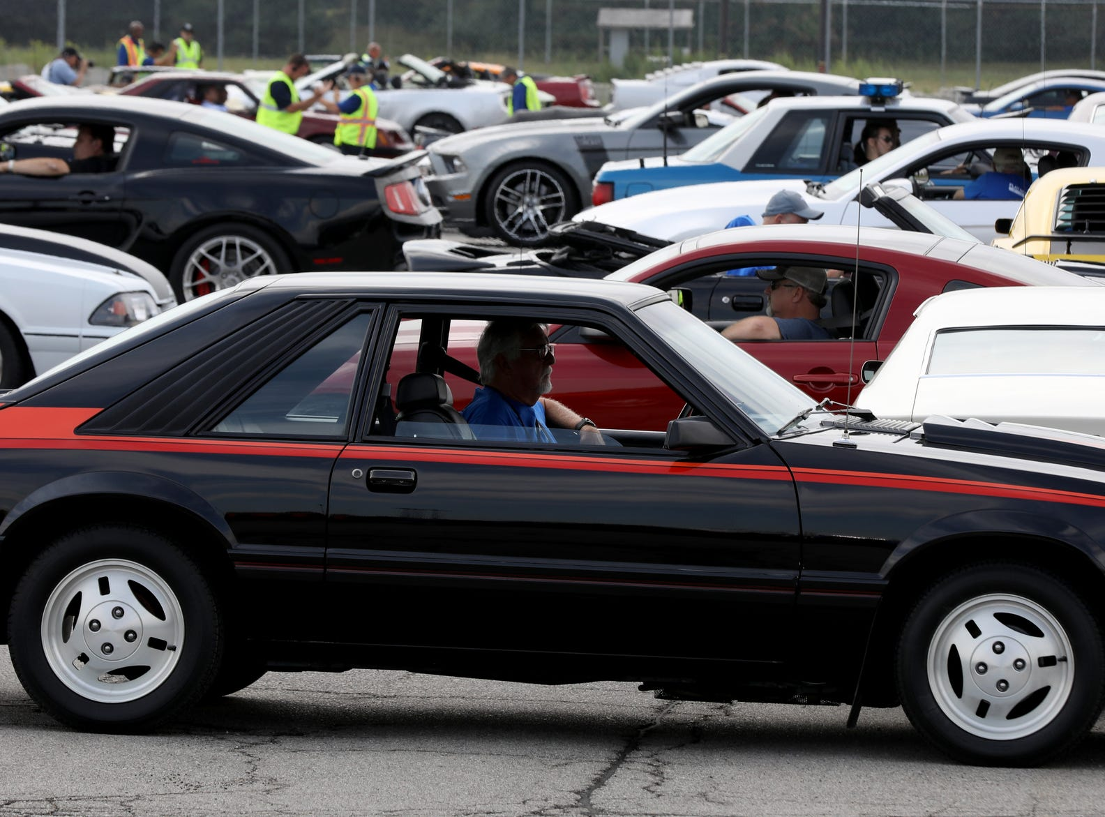 A 1980's Ford Mustang makes its way past other Mustangs during the celebration of the 10 millionth Mustang at the Ford Motor Company Flat Rock Assembly Plant in Flat Rock on Wednesday, August 8, 2018