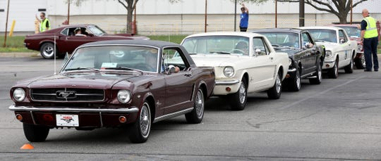 Ford Mustangs from the 1960s line up during the celebration of the 10 millionth Mustang at the Ford Flat Rock assembly plant in Flat Rock on Wednesday, Aug. 8, 2018.