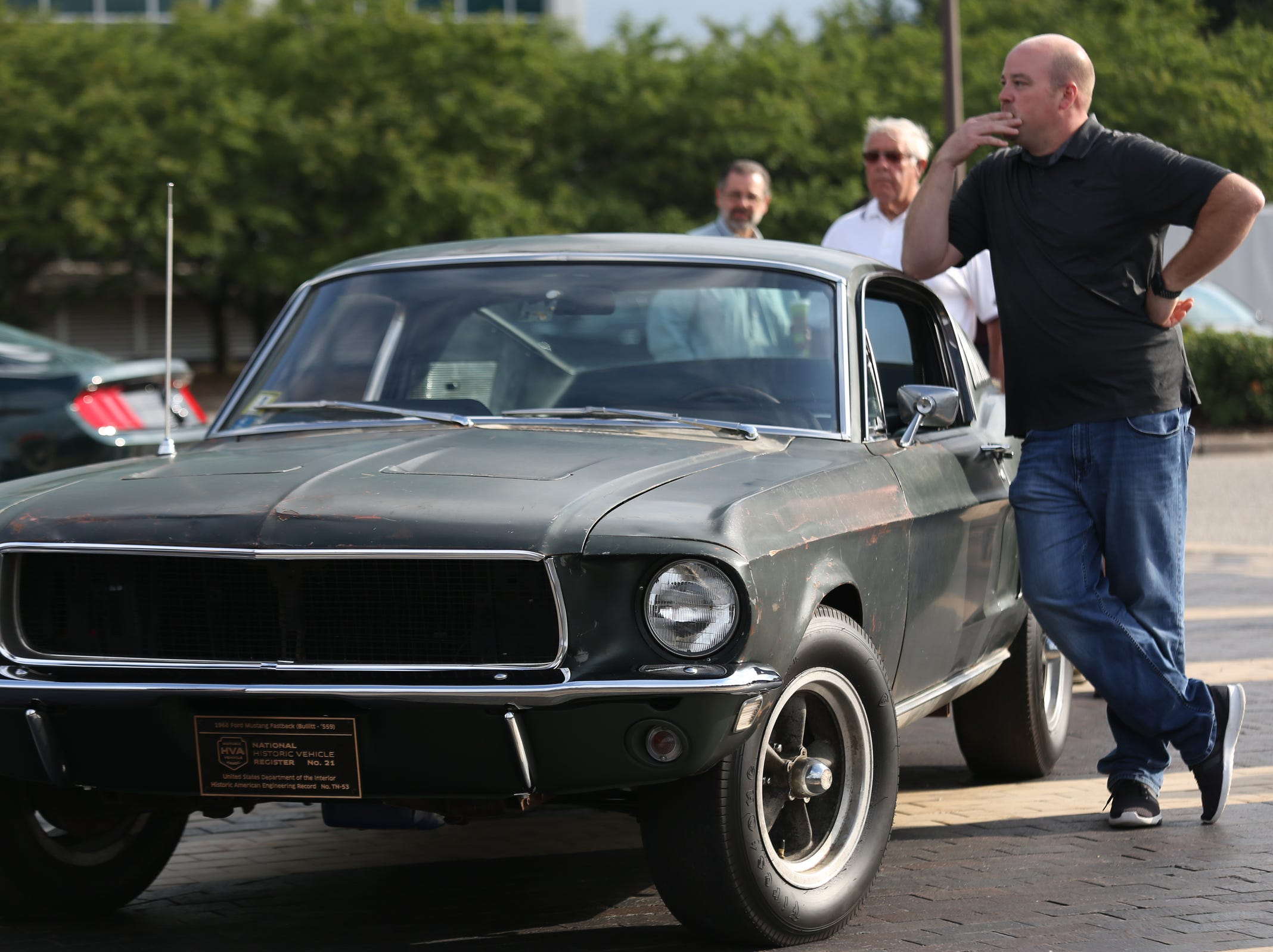 Sean Kiernan, of Nashville, stands next to the Ford Mustang GT 390 driven by Steve McQueen in the cult classic film Bullitt that his family has owned for 66 years while it is displayed during a Ford event celebrating the 10,000,000 Mustang built at the Ford Motor Company World Headquarters in Dearborn on Wed., Aug 8, 2018.