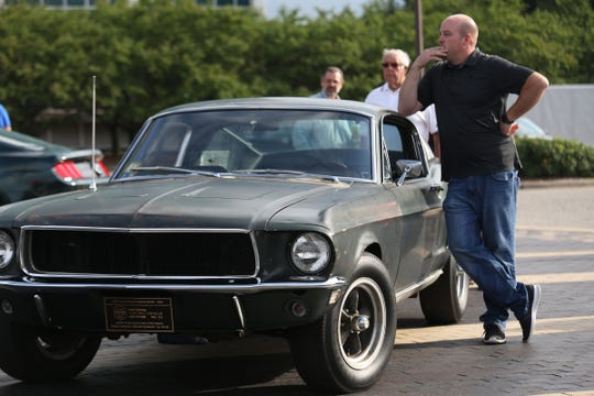 "Sean Kiernan of Nashville stands next to the Ford Mustang GT 390 driven by Steve McQueen in the cult classic film ""Bullitt."" Kiernan's family has owned the car since 1974. Here, it was part of the 10 millionth Mustang celebration at Ford World Headquarters in Dearborn on Aug. 8, 2018."