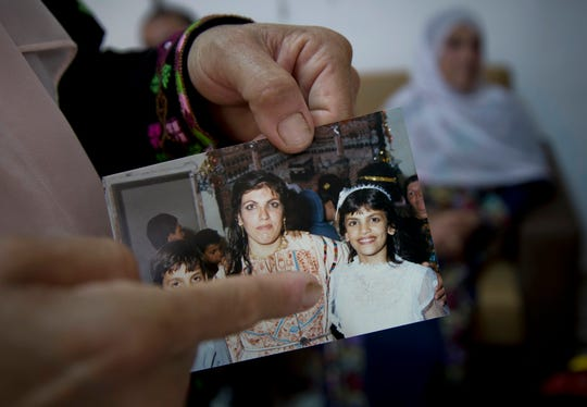 In this Wednesday, Aug. 8, 2018, photo, Fadwa Tlaib, an aunt of Rashida Tlaib points to a young Rashida in a 1987 picture with her mother Fatima and brother Nader, at the family house, in the West Bank village of Beit Ur al-Foqa. The Michigan primary victory of Tlaib, who is expected to become the first Muslim woman and Palestinian-American to serve in the U.S. Congress, is rippling across the Middle East.