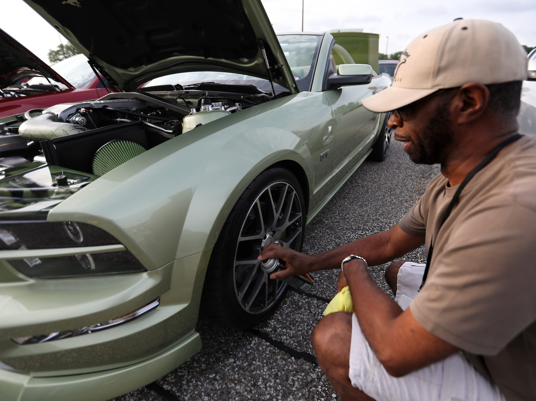Peter Dunbar, 63, of Detroit sprays tire shine on the wheels of his 2006 Ford Mustang GT convertible, during a Ford event celebrating the 10,000,000 Mustang built at the Ford Motor Company World Headquarters in Dearborn on Wed., Aug 8, 2018.