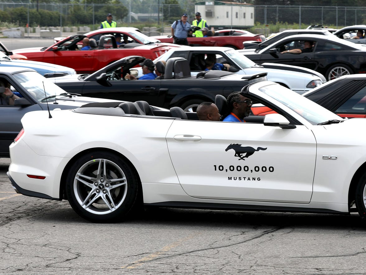 The 10 millionth Ford Mustang, a 450 horsepower 2019 Wimbledon White GT V8 makes its way past older model Mustangs in the parking lot of the Flat Rock Assembly plant during the celebration of the 10 millionth Mustang at the Ford Motor Company Flat Rock Assembly Plant in Flat Rock on Wednesday, August 8, 2018.