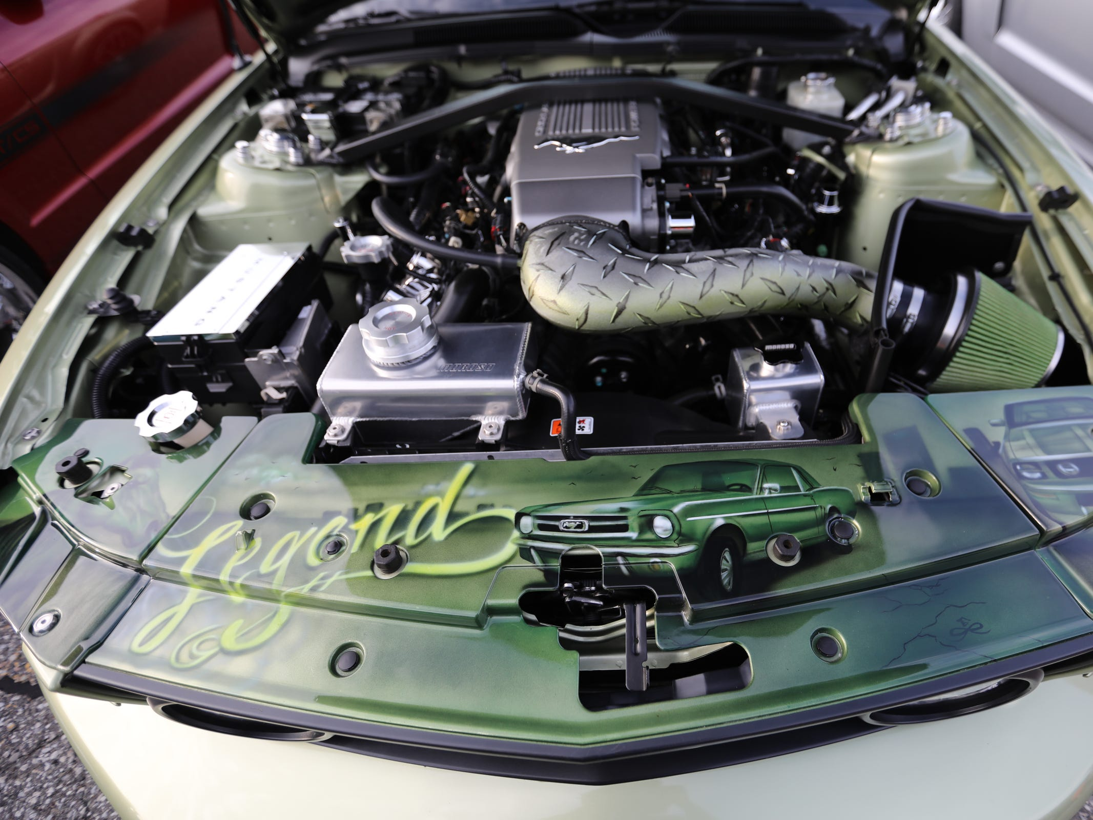 The engine of a 2006 Ford Mustang GT convertible owned by Peter Dunbar, 63, of Detroit has a custom paint job seen at the Ford World Headquarters in Dearborn on Wednesdau, Aug 8, 2018, during an event celebrating the 10 millionth Mustang.