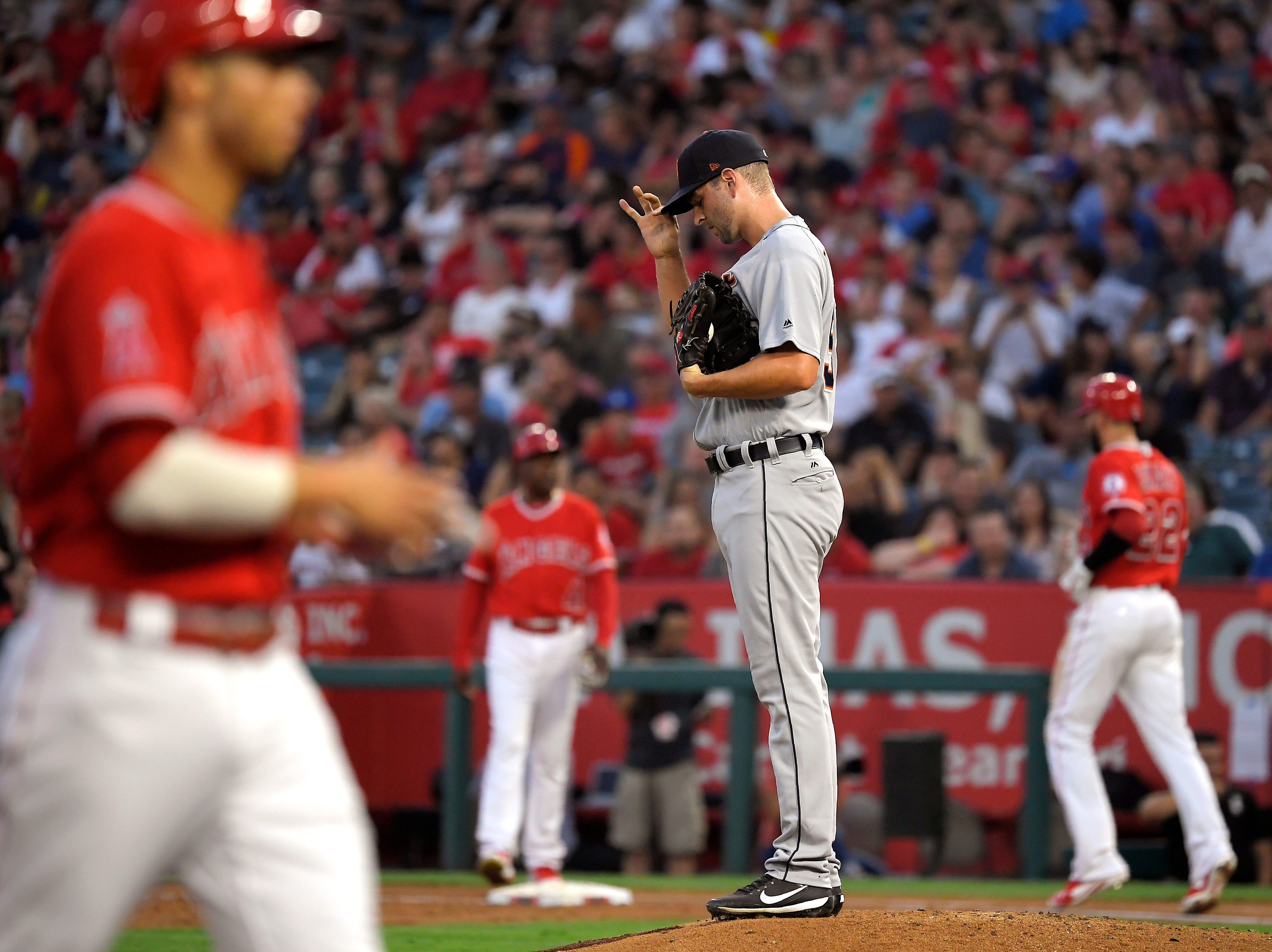 Tigers pitcher Jacob Turner, second from right, adjust his cap after walking in a run as Angels shortstop Andrelton Simmons, left, takes third and third baseman Kaleb Cowart, right, takes first during the first inning on Tuesday, Aug. 7, 2018, in Anaheim, Calif.