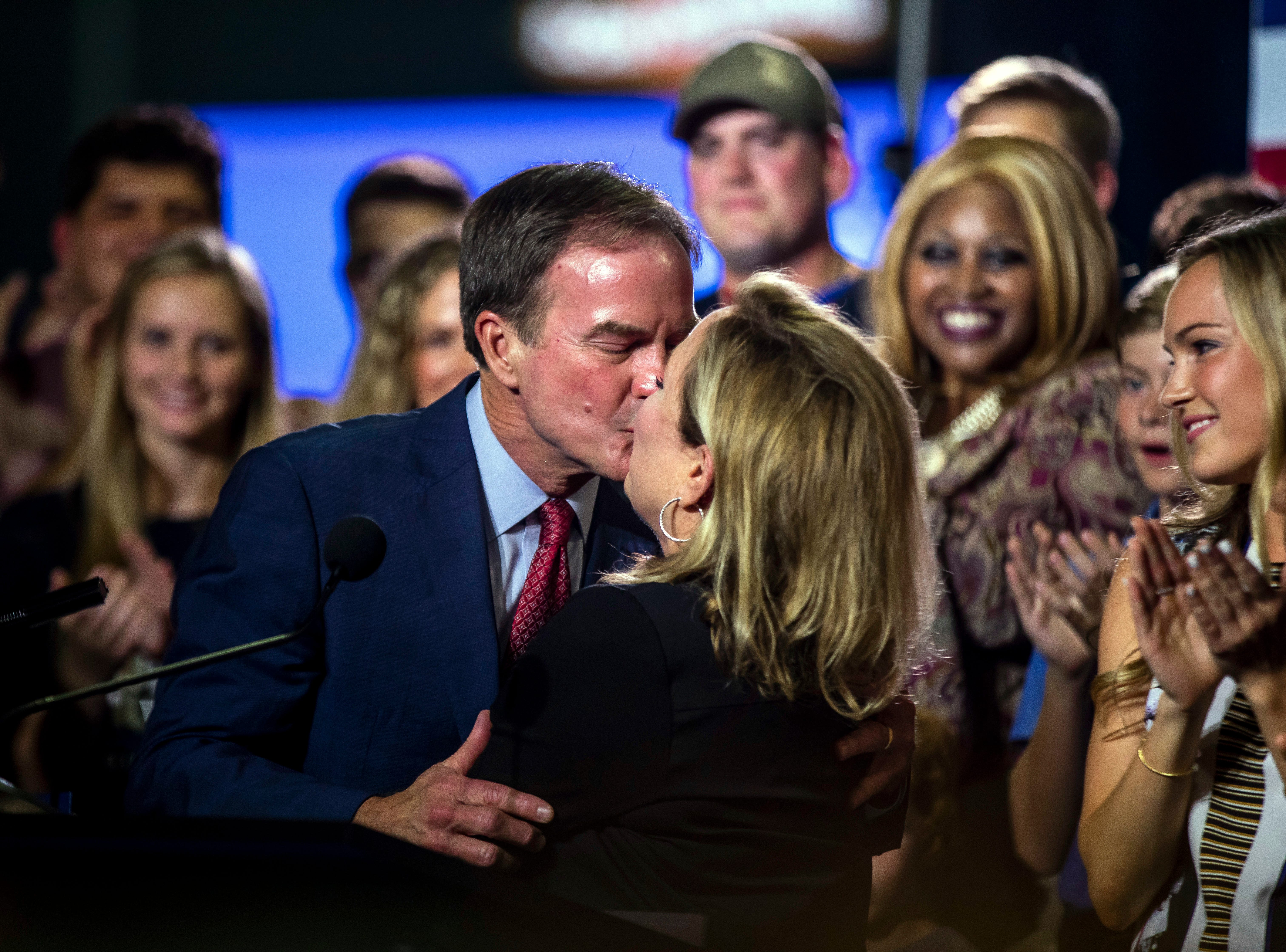Michigan Attorney General Bill Schuette kisses his wife, Cynthia, as he's surrounded by family, friends and supporters, Tuesday, Aug. 7, 2018, in Midland, Mich.