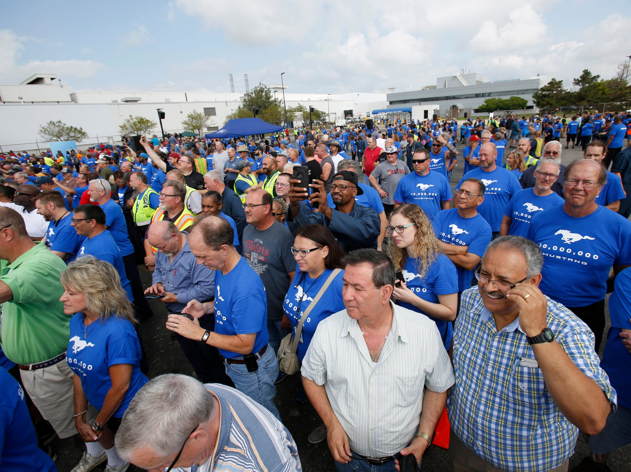 Flat Rock Assembly workers watch as a Mustang parade moves onto the parking lot during the celebration of the 10 millionth Mustang at the Ford Motor Company Flat Rock Assembly Plant in Flat Rock on Wednesday, August 8, 2018